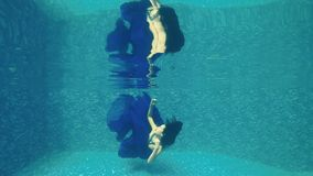 La muchacha hermosa en vestido azul largo nada debajo del agua en piscina almacen de metraje de vídeo