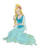 La muchacha hermosa en vestido azul se peina el pelo en un fondo blanco Imagen de archivo
