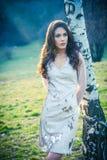 La muchacha hermosa en vestido de la moda hace una pausa el abedul Imagen de archivo libre de regalías