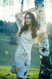 La muchacha hermosa en vestido de la moda hace una pausa el abedul Imágenes de archivo libres de regalías