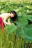 La muchacha hermosa en vestido de la tradición juega en el jardín del loto Foto de archivo