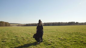 La muchacha hermosa en vestido negro largo camina en campo almacen de video