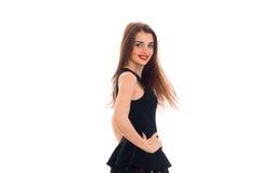 La muchacha hermosa en vestido negro vale el dar vuelta de lado a la cámara que sonríe y que guarda su mano en el lado Imagen de archivo