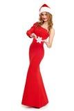 La muchacha hermosa en vestido rojo y el sombrero de santa aislados en el fondo blanco, concepto del día de fiesta de la Navidad, Fotos de archivo