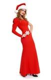 La muchacha hermosa en vestido rojo y el sombrero de santa aislados en el fondo blanco, concepto del día de fiesta de la Navidad, Fotografía de archivo libre de regalías
