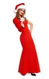 La muchacha hermosa en vestido rojo y el sombrero de santa aislados en el fondo blanco, concepto del día de fiesta de la Navidad, Imagenes de archivo