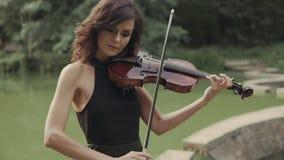 La muchacha hermosa en vestido toca el violín al aire libre Violinista elegante en bosque almacen de video