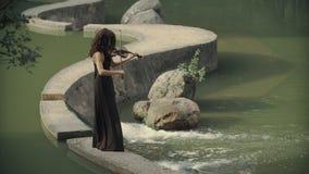 La muchacha hermosa en vestido toca el violín al aire libre Violinista elegante en bosque almacen de metraje de vídeo