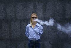 La muchacha hermosa en vidrios con placer fuma un vape, día, al aire libre Fotografía de archivo libre de regalías
