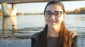 La muchacha hermosa en vidrios está mirando en la cámara y la sonrisa Sonrisa encantadora Contra la perspectiva del río con metrajes