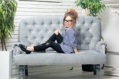 La muchacha hermosa en vidrios se sienta en estudios de un sofá del azul Fotos de archivo libres de regalías