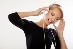La muchacha hermosa es escucha la música Foto de archivo