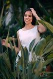 La muchacha hermosa es relajante en fondo natural Una mujer joven alegre en verde deja el fondo Una señora de moda fotos de archivo