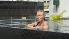 La muchacha hermosa es relajante en una piscina del infinito almacen de video