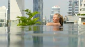 La muchacha hermosa es relajante en una piscina del infinito metrajes