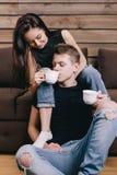 La muchacha hermosa está bebiendo a un individuo con té Fotografía de archivo libre de regalías