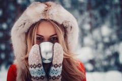 La muchacha hermosa está bebiendo una bebida caliente de la taza en el invierno adentro Fotos de archivo libres de regalías