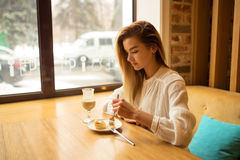 La muchacha hermosa está comiendo la torta Foto de archivo libre de regalías