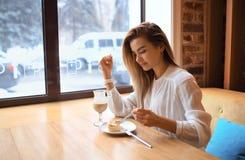 La muchacha hermosa está comiendo la torta Fotos de archivo libres de regalías