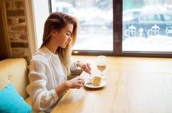 La muchacha hermosa está comiendo la torta Imagen de archivo