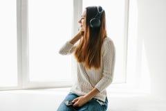 La muchacha hermosa está escuchando la música al lado de la ventana Imágenes de archivo libres de regalías