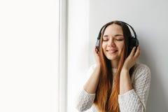 La muchacha hermosa está escuchando la música al lado de la ventana Foto de archivo