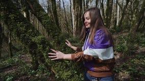 La muchacha hermosa está frotando ligeramente el tronco de árbol que se cubre con el musgo verde grueso almacen de metraje de vídeo
