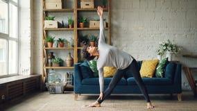 La muchacha hermosa está haciendo los ejercicios de la yoga en casa que estiran el cuerpo que se coloca en casa en el piso concen almacen de metraje de vídeo