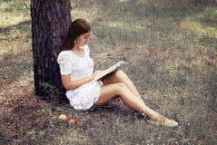 La muchacha hermosa está leyendo el libro interesante Foto de archivo libre de regalías