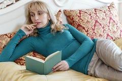 La muchacha hermosa está leyendo un libro en el dormitorio, en la cama con imágenes de archivo libres de regalías