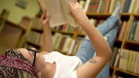 La muchacha hermosa está leyendo un libro que miente en el piso en la biblioteca almacen de video