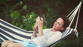 La muchacha hermosa está mintiendo en hamaca y está jugando con su smartphone