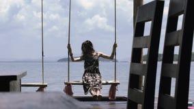 La muchacha hermosa está montando en un oscilación contra el mar en un café en el embarcadero almacen de video
