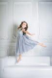 La muchacha hermosa está saltando en el sofá Fotos de archivo