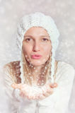La muchacha hermosa está soplando los copos de nieve fotografía de archivo