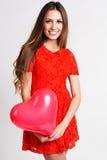 La muchacha hermosa está sosteniendo los globos rojos del corazón Imagenes de archivo