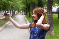 La muchacha hermosa está tomando un selfie al aire libre Foto de archivo libre de regalías