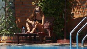 La muchacha hermosa exprime hacia fuera las piernas de las manchas de la protección solar