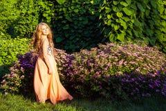 La muchacha hermosa feliz con el pelo marrón claro largo está presentando en el parque Imagen de archivo libre de regalías