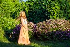 La muchacha hermosa feliz con el pelo marrón claro largo está presentando en el parque Foto de archivo libre de regalías