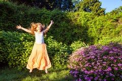 La muchacha hermosa feliz con el pelo marrón claro largo está presentando en el parque Fotografía de archivo libre de regalías