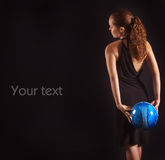 La muchacha hermosa guarda el balón de fútbol azul en el CCB negro fotografía de archivo libre de regalías