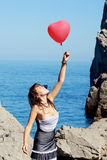 La muchacha hermosa guarda la bola de aire cerca del mar Fotos de archivo libres de regalías