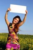 La muchacha hermosa guarda a una tarjeta blanca Imagen de archivo