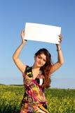 La muchacha hermosa guarda a una tarjeta blanca Fotos de archivo