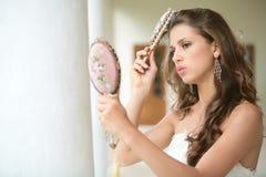La muchacha hermosa hace el peinado Imagen de archivo libre de regalías