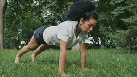 La muchacha hermosa hace estirar ejercicios en hierba en parque almacen de metraje de vídeo
