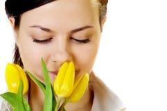 La muchacha hermosa huele tulipanes amarillos Fotografía de archivo