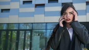 La muchacha hermosa joven aumenta su teléfono y contesta a la llamada almacen de video