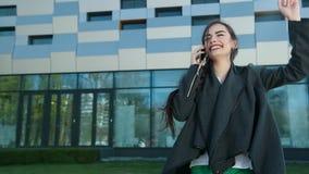La muchacha hermosa joven aumenta su teléfono y las respuestas llaman almacen de metraje de vídeo